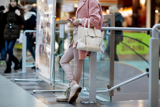 Stylish young girl standing in a pink coat in a shop and look into the phone