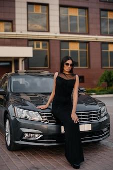 Стильная молодая девушка стоит возле машины в черном платье. деловая мода и стиль.