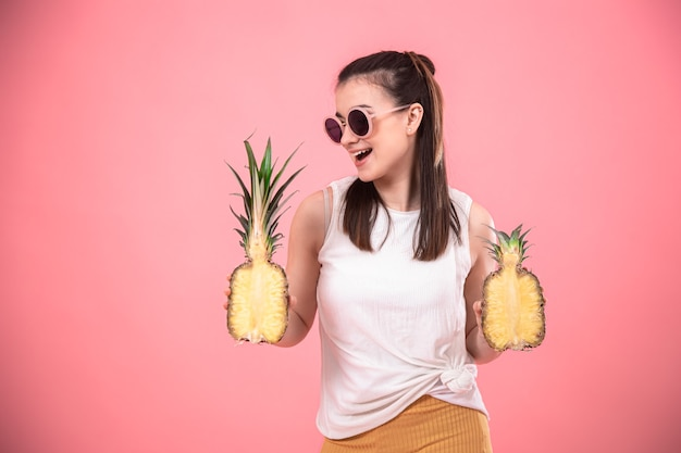 Stylish young girl in sunglasses smiles and holds fruits. summer vacation concept.