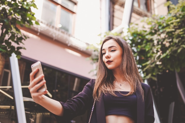 Stylish young girl takes a selfie. girl makes her photo on smartphone.