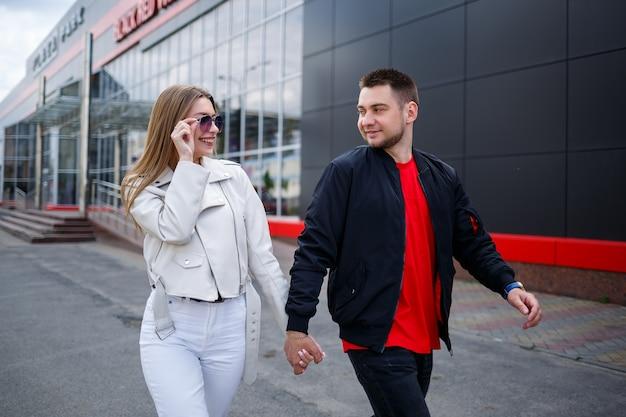 ヨーロッパ風のブロンドの髪と黒いジャケットの男を持つスタイリッシュな若い女の子。恋愛中のカップルのアーバンウォーク、カジュアルスタイルのモダンファッション。幸せな関係の概念