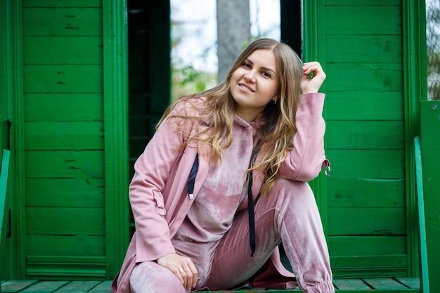 Стильная молодая девушка со светлыми волосами европейской внешности сидит на ступеньках, одетая в розовый костюм, повседневную одежду