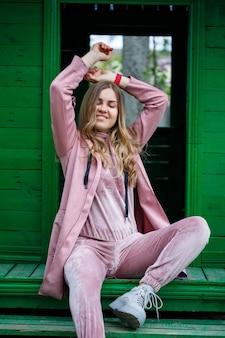 Стильная молодая девушка со светлыми волосами европейской внешности сидит на ступеньках, одетая в розовый костюм, современная женская мода, повседневная одежда