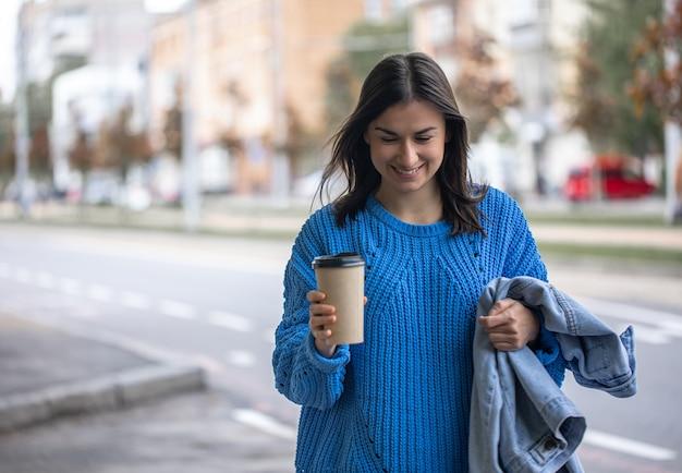 Стильная молодая девушка с кофе пойти на прогулку.