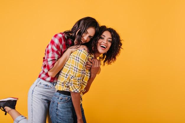 Giovani ragazze alla moda sciocco. la signora in camicetta rossa è saltata addosso a sua sorella per divertimento.