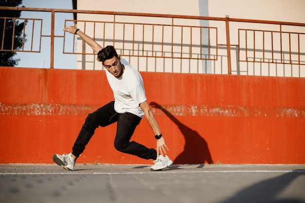 청바지와 흰색 티셔츠를 입은 세련된 젊은이가 화창한 날 페인트 칠한 콘크리트 벽에 기대어 거리에서 브레이크 댄스를 추고 있습니다.