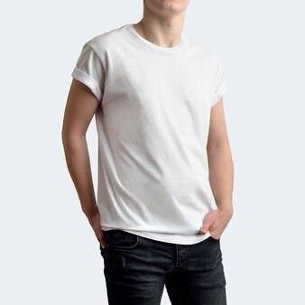 스튜디오의 깨끗한 흰색 배경에 빈 티셔츠와 검은색 바지를 입은 세련된 젊은 남자. 주머니에 손을 넣고 몸을 약간 돌린 정면 포즈. 모형은 쇼케이스에서 사용할 수 있습니다.