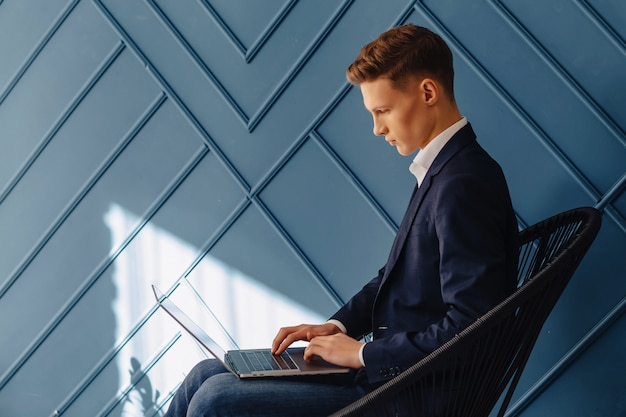 Stylish young guy with laptop, young businessman, freelancer work, aqua background