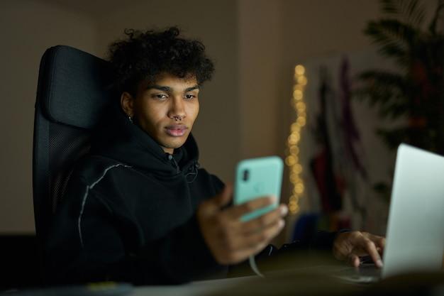 Стильный молодой парень с пирсингом, глядя на экран смартфона, сидя за столом, используя