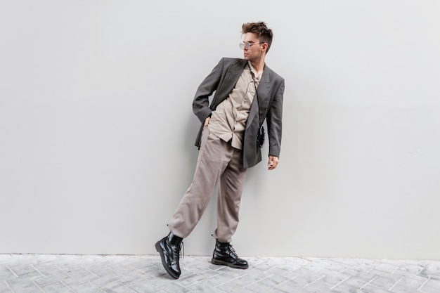 Stylish young guy with sunglasses in fashion casual clothes look with jacket, shirt, trousers and boots walks near gray wall in city