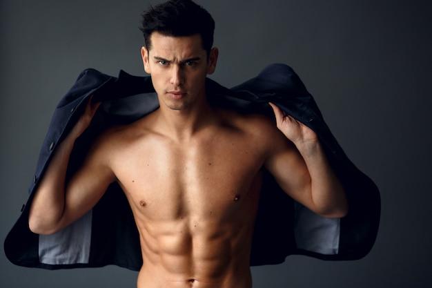 スタイリッシュな若いハンサムな男立ち、裸の胴体にファッショナブルなスーツでポーズ