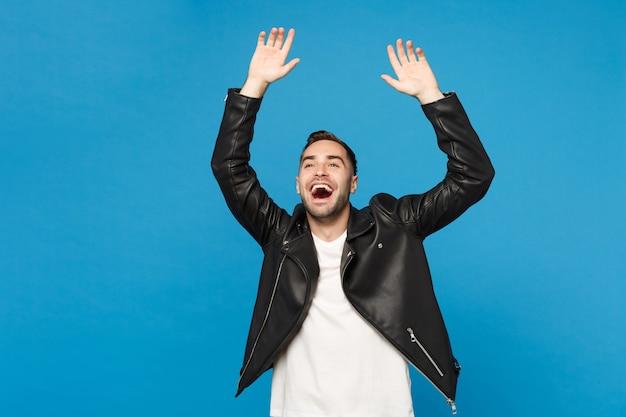 검은 가죽 재킷 흰색 티셔츠를 입은 세련된 젊은 행복한 남자가 승자 제스처를 하고 파란색 벽 배경 스튜디오 초상화에 격리된 예라고 말합니다. 사람들이 진실한 감정 개념입니다. 모의 복사 공간
