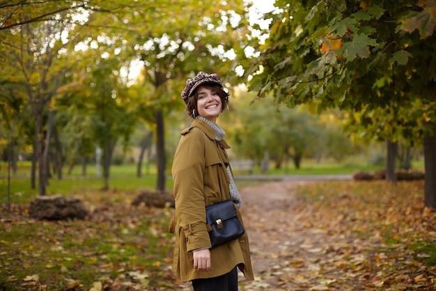 Elegante giovane bella signora bruna dai capelli corti felice con l'acconciatura bob guardando indietro e sorridendo allegramente mentre si cammina attraverso il parco in una calda giornata autunnale
