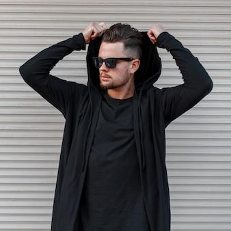 현대 금속 벽 근처에 후드를 입고 검은 유행 운동복에 검은 색 티셔츠에 어두운 선글라스에 세련된 헤어 스타일로 수염을 가진 세련된 젊은 힙 스터 남자