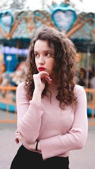 カルーセルと公園で屋外でポーズをとるスタイリッシュな若い流行に敏感な女性
