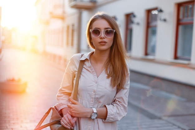 Stylish young hipster woman in stylish sunglasses in a trendy white dress with a fashionable brown leather bag, posing outdoors against a background of vintage buildings and sunlight. cute girl