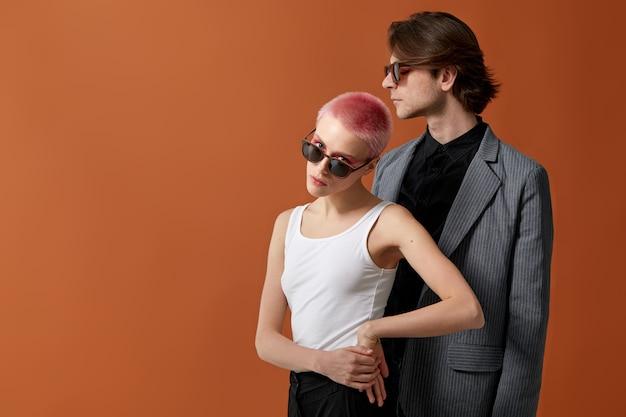 ピンクの短い髪とサングラスの男と一緒にポーズをとって、スタイリッシュな若いヒップスターのセクシーな女性