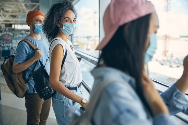 Stylish young lady with backpack wearing protective mask while waiting for a flight with her friends in the international airport