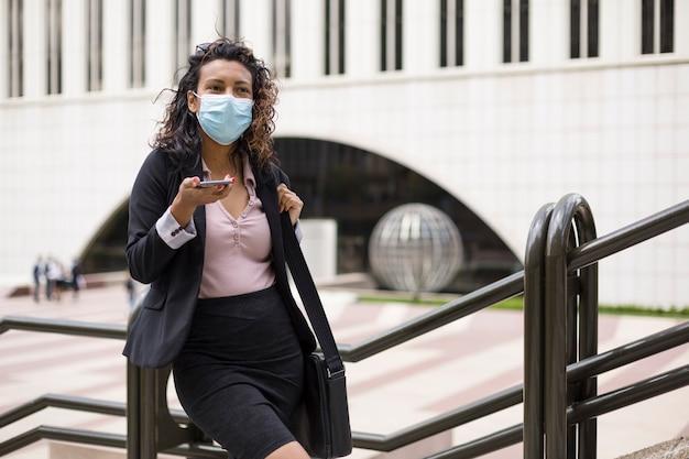 얼굴 마스크를 쓴 세련된 젊은 라티나 여성. covid-19 동안 근무일에 진취적인 사람.