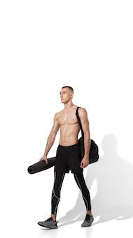 흰색 스튜디오 배경, 그림자와 초상화에 연습 세련 된 젊은 남자 선수. 스포티 한 핏 모델은 모션과 액션에서 작동합니다. 바디 빌딩, 건강한 라이프 스타일, 스타일 컨셉.