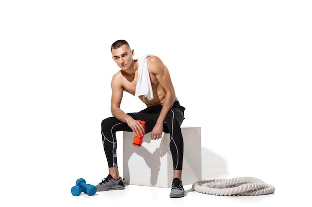 白いスタジオの背景、影の肖像画で練習しているスタイリッシュな若い男性アスリート。スポーティーフィットモデルは、動きとアクションでうまくいきます。