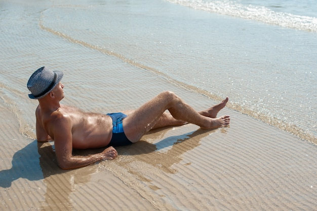 Stylish young male model man lying on beach sand
