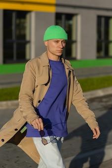 녹색 모자, 거리에 밝은 회색 벽과 갈색 재킷을 입고 세련된 젊은 남성 모델