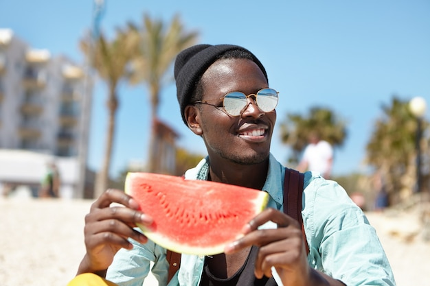 Stylish young male spending leisure time at seaside
