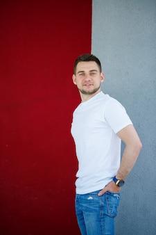 スタイリッシュな若い男、灰色と赤の壁の背景に立っている白い空白のtシャツを着た男。アーバンスタイルの服、モダンでファッショナブルなイメージ。メンズファッション