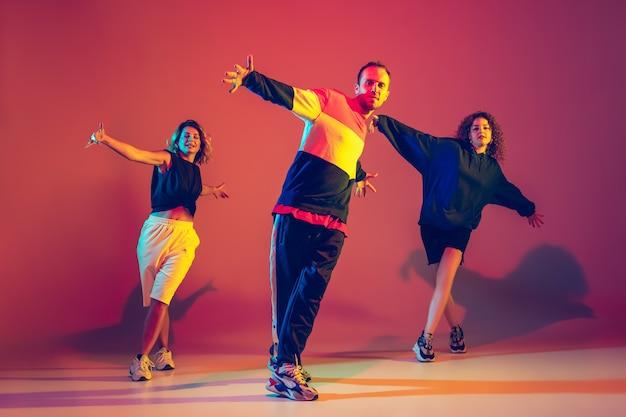 ネオンの光のダンスホールでグラデーションの背景に明るい服を着てヒップホップを踊るスタイリッシュな若い男性と女性。若者文化、動き、スタイルとファッション、アクション、ヒップホップ。ファッショナブルな肖像画。