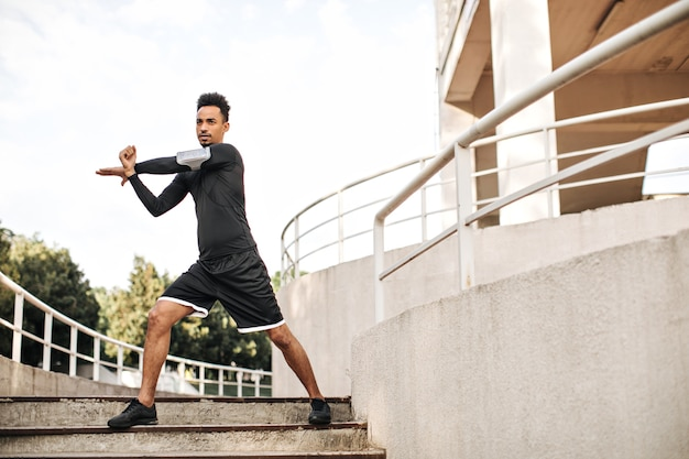 Stylish young man in black sport shorts and long-sleeved t-shirt stretches and works out outdoors on stairs