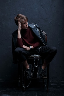 Stylish young man in a black vintage jacket in a red warm golf in stylish pants in trendy sneakers with a metal chain sits on a wooden chair in a room near the wall. attractive trendy modern guy