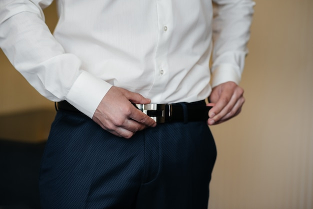 Stylish young man buttoning the cuff links on the sleeves. style.
