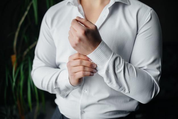 Стильный молодой человек застегивает запонки на рукавах. стиль