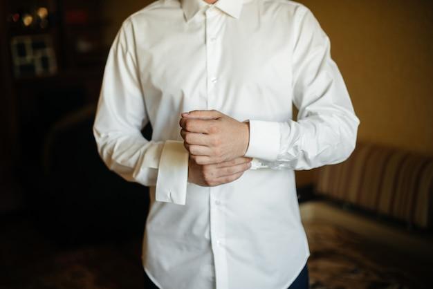 Стильный молодой человек застегивает запонки на рукавах. стиль.