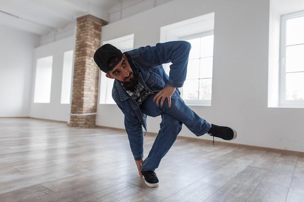 Стильный молодой человек танцор с джинсами в джинсовой одежде танцует в танцевальной студии
