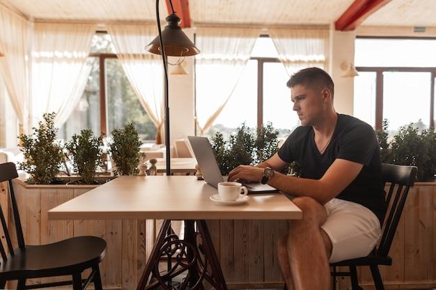 Стильный молодой человек-фрилансер в модной одежде сидит за столиком в винтажном кафе и работает на современном ноутбуке во время обеда.