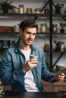 Stylish young man holding cup of coffee and digital tablet in hands