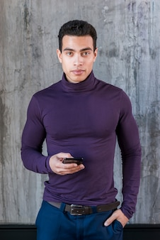 A stylish young man holding mobile phone in his hand looking at camera standing against grey wall
