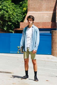 Stylish young man holding skateboard standing outside
