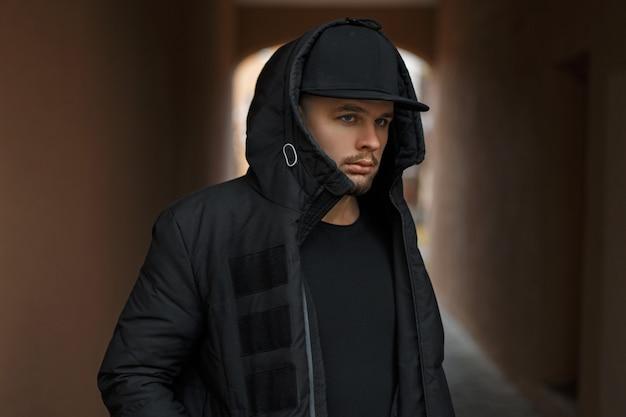 거리에 후드와 함께 검은 겨울 따뜻한 재킷에 야구 모자에 세련된 젊은 남자