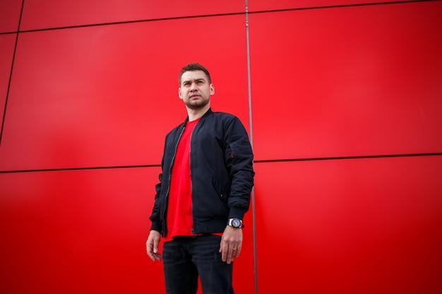 屋外の赤い建物の近くで晴れた日にポーズをとるヴィンテージブルージーンズのサングラスでファッショナブルなtシャツを着たスタイリッシュな若い男。通りの現代人。ユーススタイル