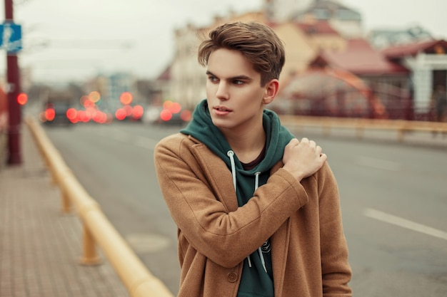 거리에 까마귀와 트렌디 한 빈티지 코트에 세련된 젊은 남자