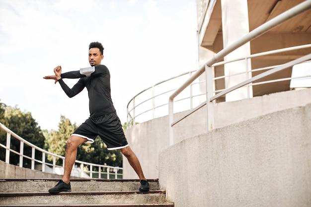 黒のスポーツショーツと長袖のtシャツを着たスタイリッシュな若い男が伸びて、屋外の階段で運動します