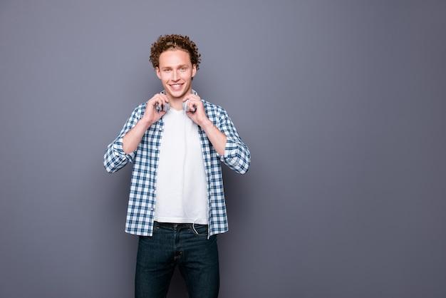 カジュアルな市松模様のシャツとイヤホンを保持しているジーンズのスタイリッシュな若い男