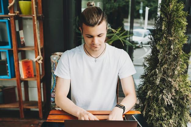 카페 테이블에 앉아 현대 노트북 키보드에 입력하는 캐주얼 복장에 세련된 젊은 남자