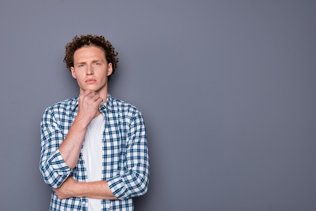 市松模様のシャツの手あご思考のスタイリッシュな若い男
