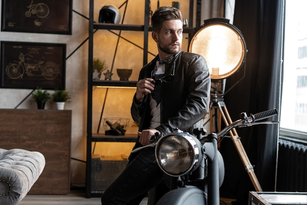 Стильный молодой человек в кожаной куртке, сидя на мотоцикле.