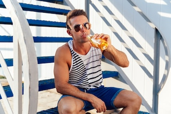 Stylish young man in sunglasses drinking a cold beer while sitting on stairs at sunny day