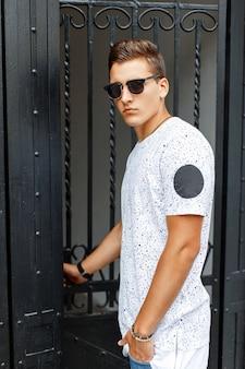 白いシャツとサングラスのスタイリッシュな若い男がドアに来る